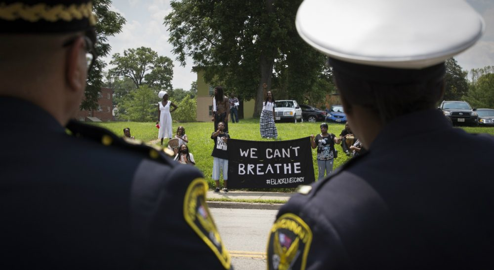 It's time for hard-headed examination of how too many officers treat African-Americans. One place to look for answers, ironically, is Cincinnati. In this photo, Cincinnati police look at protesters across the street from funeral services for Samuel Dubose, Tuesday, July 28, 2015. Dubose was fatally shot by a University of Cincinnati police officer who stopped him for a missing license plate. (John Minchillo/AP)