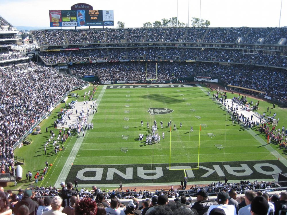 The Oakland Raiders are among three NFL teams with proposals on the table for new stadiums. But do professional sports stadiums help or hurt their neighborhoods? (Chris Yunker/Flickr)
