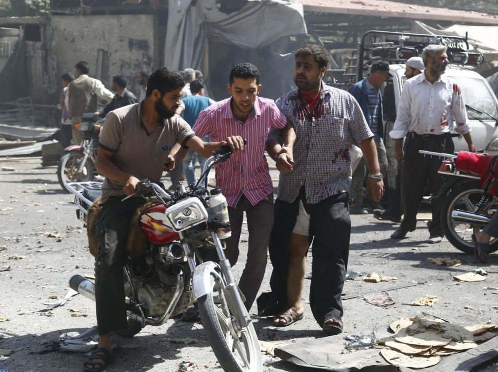 Syrian men react at the scene of reported air strikes by regime forces in the rebel-held Eastern Ghouta area near Damascus today. At least 31 civilians were killed in Syrian government air strikes near Damascus as a barrage of deadly rebel rocket fire hit the capital, a monitor said. (Sameer al-Doumy/Getty Images)