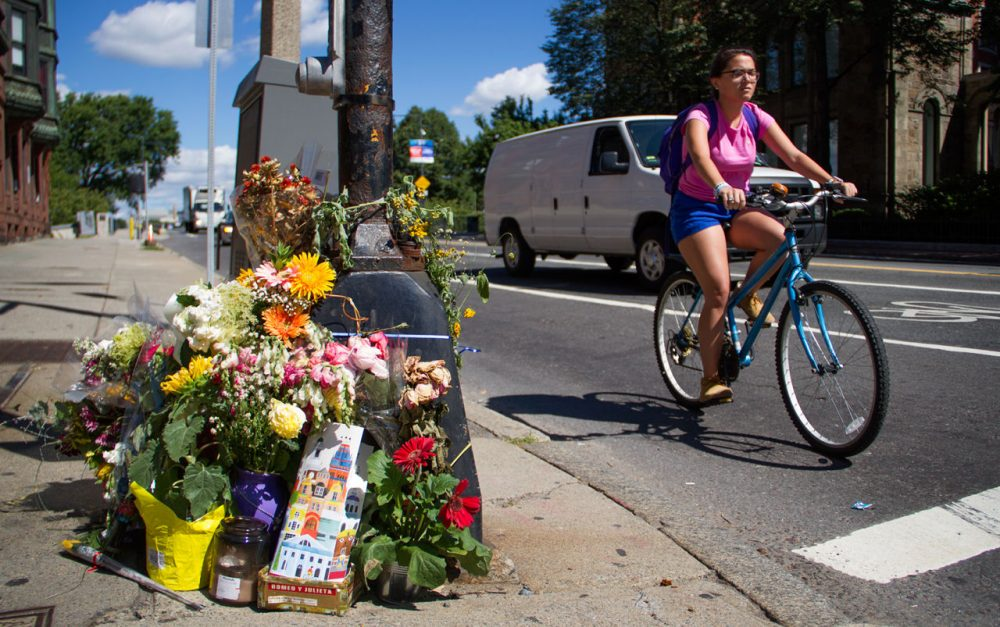 A bicyclist rides past the Boston intersection of Mass. Ave. and Beacon Street, where Anita Kurmann, 38, was hit and killed in a crash last fall. (Hadley Green for WBUR)
