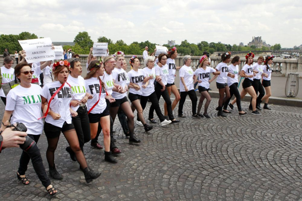 Femen activists chanting slogans and carrying signs reading: Abolition of Prostitution, No Demand No Offer, walk towards the French National Assembly in Paris on June 12 as part of a demonstration asking for the abolition of prostitution. (Remy de la Mauviniere/AP)
