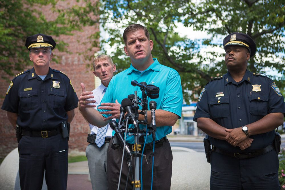 Boston Mayor Marty Walsh speaks Thursday in Roxbury about shootings that left three dead in the city. He's flanked by Boston Police Department officials.  (Jesse Costa/WBUR)