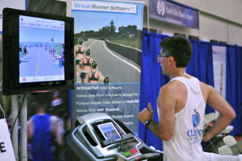 Joe Ciavattone, an employee of Outside Interactive, demonstrates the company's virtual race technology at the New Balance Falmouth Road Race expo. The company is partnering with the race to let runners compete on a treadmill virtually from anywhere while watching video footage of the actual 7-mile course. (Collin Binkley/AP)