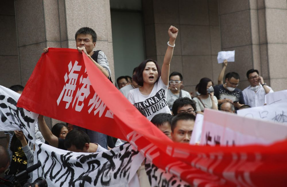 Residents, whose homes were destroyed in the explosion at a chemical warehouse last week, protest outside the hotel where authorities are holding a press conference in Tianjin on August 17, 2015. (STR/AFP/Getty Images)