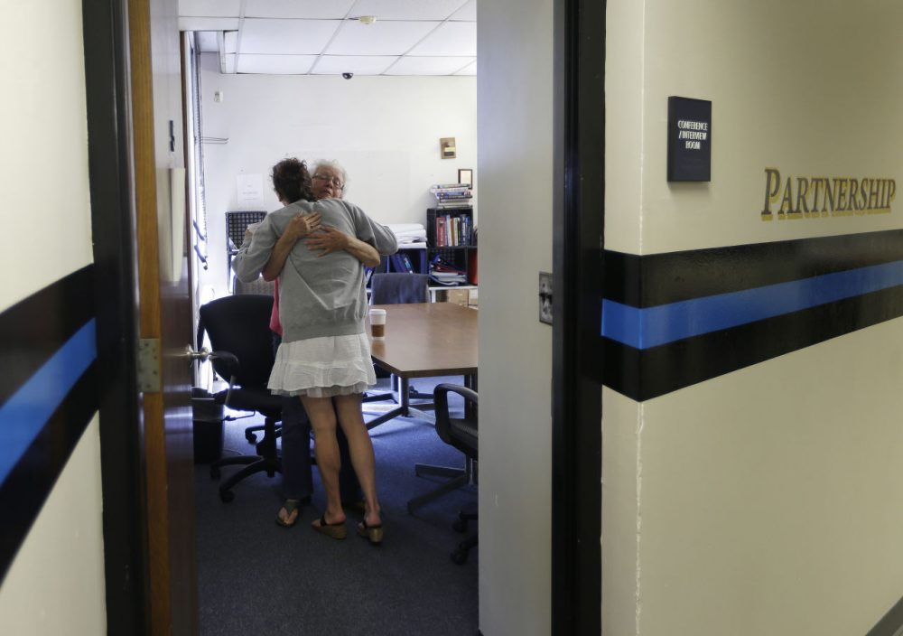 In this July 10, 2015, photo, volunteer Ruth Cote, facing, hugs a woman inside the police station in Gloucester, Mass., who has voluntarily come to the police for help kicking her heroin addiction. Gloucester is taking a novel approach to the war on drugs, making the police station a first stop for addicts on the road to recovery. Addicts can turn in their drugs to police, no questions asked, and officers, volunteers and trained clinicians help connect them with detox and treatment services. (Elise Amendola/AP)