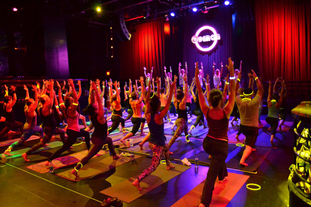 About 50 people participate in 90 minutes of rave yoga at the Oberon in Cambridge on Aug. 5. (Photo by Alexandra Düsterfeld; Courtesy Bill Connolly of Move With)