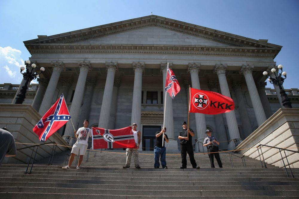 Ku Klux Klan members take part in a Klan demonstration at the state house building on July 18, 2015 in Columbia, South Carolina. The KKK protested the removal of the Confederate flag from the state house grounds and hurled racial slurs at minorities as law enforcement tried to prevent violence between the opposing groups.  (John Moore/Getty Images)