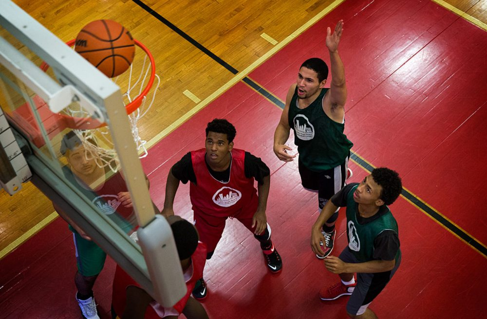Yasmany Mejia (left), Isaias Ortiz (center) and Jose Cirino (right) watch as the ball drops into the net at the One Hood Peace Basketball League championship. (Robin Lubbock/WBUR)