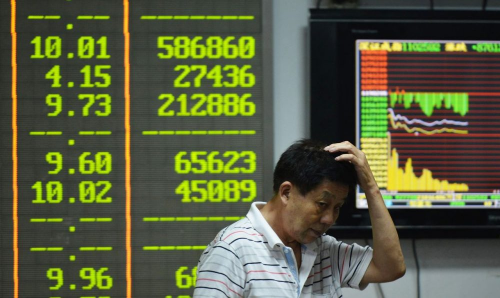 An investor gestures in front of screens showing share prices at a securities firm in Hangzhou, in eastern China's Zhejiang province on August 24, 2015. Shanghai shares nosedived 8.49 percent on August 24 as Beijing's latest market intervention failed to restore confidence, with concern mounting about the stalling economy (STR/AFP/Getty Images)