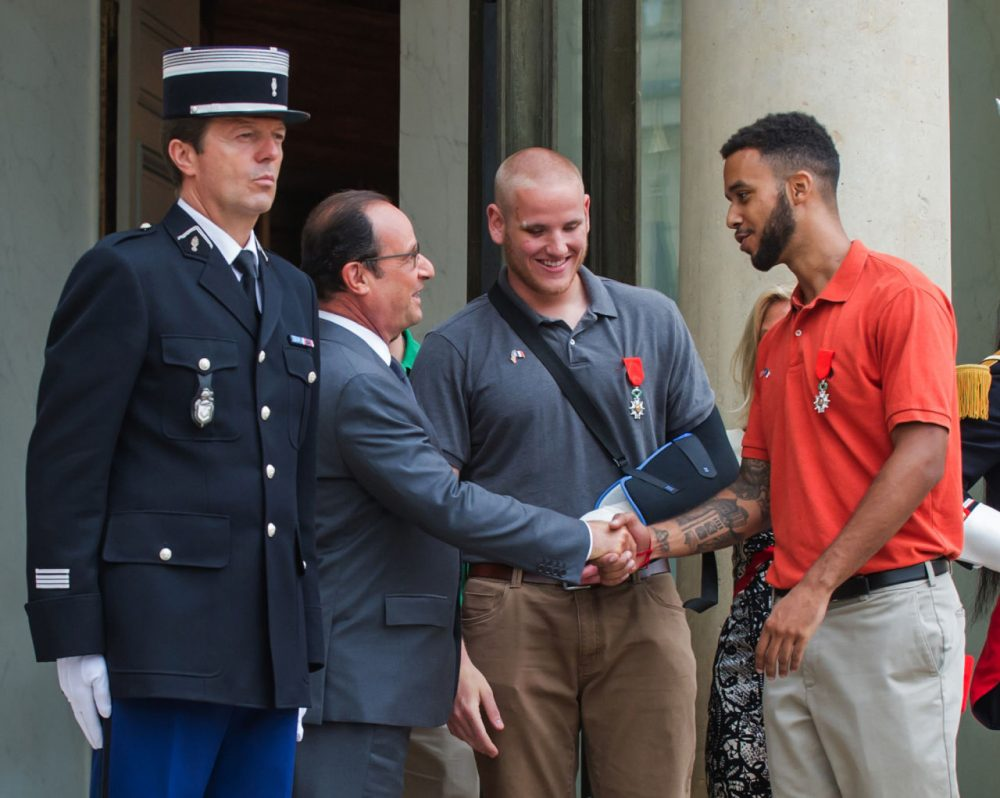 French President Francois Hollande, left, shakes hands with Anthony Sadler, right, a senior at Sacramento University in California, while U.S. Airman, Spencer Stone, looks on as they leave the Elysee Palace in Paris, France, after being awarded with the French Legion of Honor by French President,  Monday, Aug. 24, 2015.  (Kamil Zihnioglu/AP Photo)