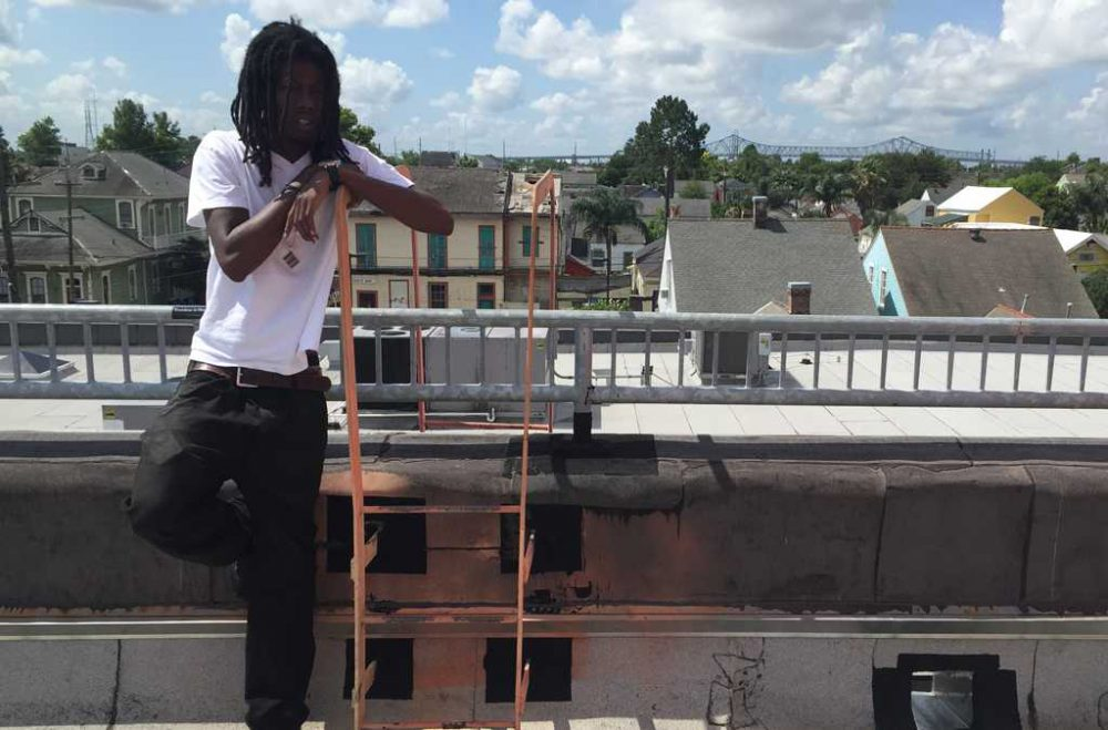 Kendall Hooker stands on the roof of the New Orleans Healing Center in the city's Marigny neighborhood. Behind him is the edge of the skyline, and the Crescent City Connection Bridge. (Laine Kaplan-Levenson)