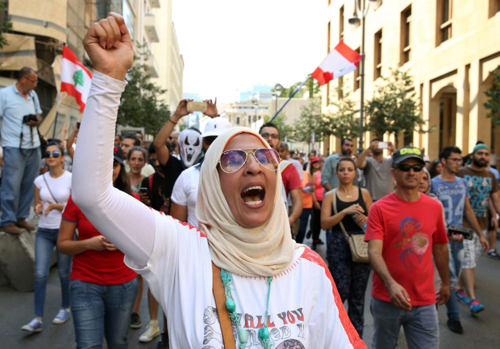 A Lebanese activist chants slogans during a protest against the ongoing trash crisis, in downtown Beirut, Lebanon, Sunday, Aug. 23, 2015. Thousands of protesters poured into central Beirut Sunday demanding government resignation hours after Prime Minister Tammam Salam hinted he might step down following violent protests against government corruption and political dysfunction triggered by a month long trash crisis in Beirut. (Bilal Hussein/AP Photo)