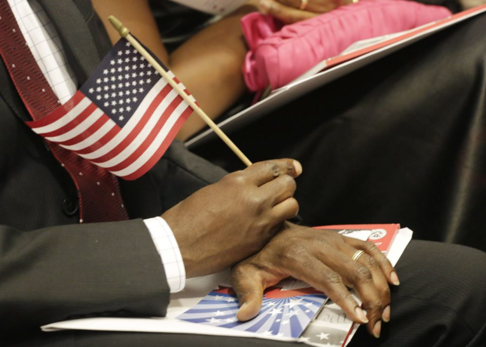 A new United States citizen holds an American flag during a naturalization ceremony, Wednesday, July 9, 2014 in New York. (Mark Lennihan/AP)