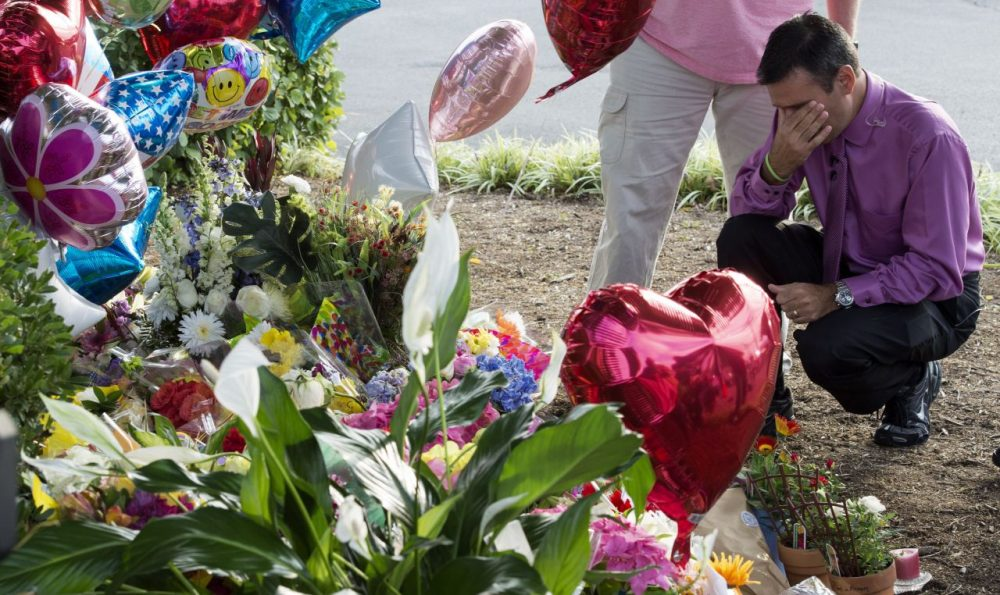 WDBJ TV weatherman Leo Hirshbrunner views the makeshift memorial with members of the crew at the gate of WDBJ's television studios August 27, 2015, in Roanoke, Virginia. The former television reporter who shot dead two journalists during a live broadcast before killing himself warned he had been a 'human powder keg... just waiting to go BOOM.' The gunman -- Vester Lee Flanagan, 41, also known as Bryce Williams --posted chilling footage of Wednesday's shocking double murder online. Reporter Alison Parker, 24, and cameraman Adam Ward, 27, were shot and killed at close range while conducting an on-air interview for WDBJ, a CBS affiliate in Roanoke, Virginia, about 240 miles southwest of Washington. Friends, family and the community at large mourned the tragedy, which renewed calls for tougher gun laws in the United States. Flanagan was said to have bought his gun legally. (Paul J. Richards/AFP/Getty Images)