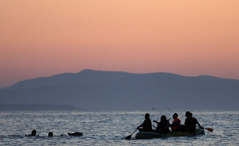 Two migrants from Syria are assisted by their friends as they swim the final 50 yards of their journey before arriving on the beach on the island of Kos after crossing a three mile stretch of the Aegean Sea in a small boat from Turkey August 28, 2015 in Kos, Greece. Migrants from the Middle East and North Africa continue to flood into Europe at a rate that marks the largest migration since World War II. (Win McNamee/Getty Images)