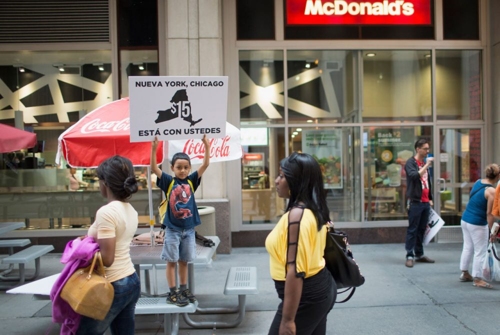 Juan Hernandez, 8, protests with his mother, who works for McDonald's, and other fast food workers and community activists outside a McDonald's restaurant in the Loop on June 22, 2015 in Chicago, Illinois. The protesters were calling for an increase in the minimum wage to $15 per hour. The demonstration was staged to coincide with the 4th hearing of the Wage Board in New York City as it debates the $15-dollar-per-hour increase for its workers. (Scott Olson/Getty Images)