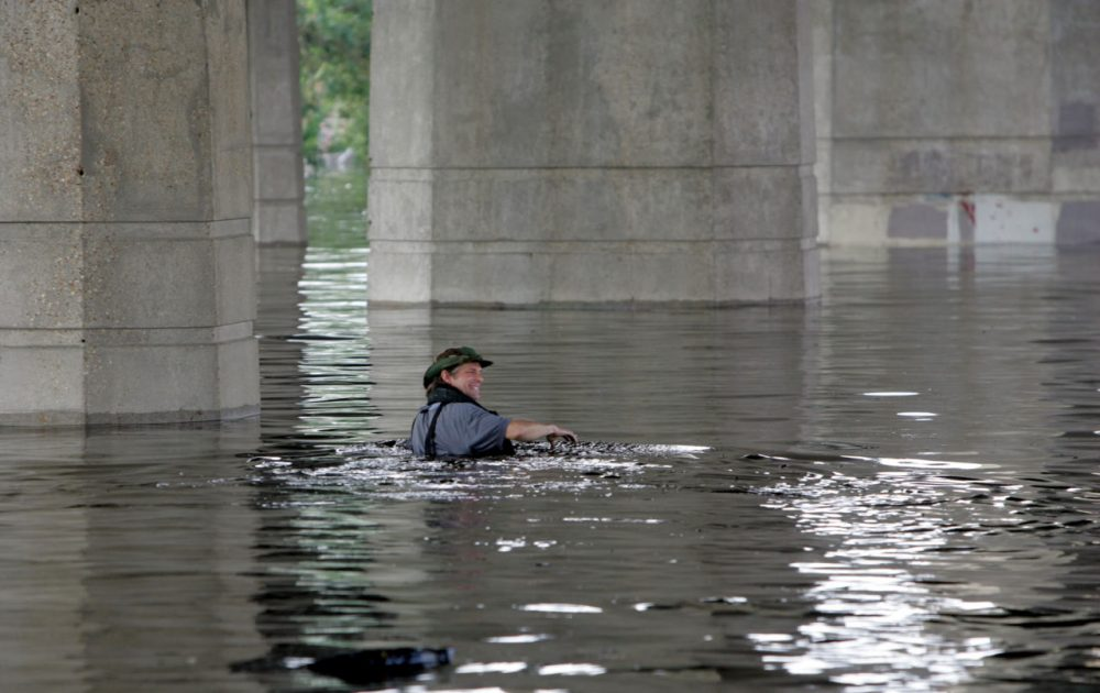 Times-Picayune staff photographer Alex Brandon swims away from the paper in the flooded city of New Orleans during the aftermath of Hurricane Katrina on Tuesday, Aug. 30, 2005. Brandon had swam to the building to get a memory card of photos to the paper. (Bill Haber/AP)