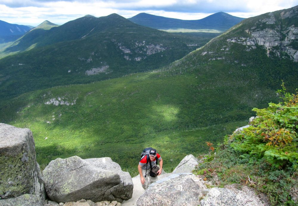 A hiker climbs up Mount Katahdin with the wilderness of Baxter State Park in Maine in the background, Aug. 27, 2014. Katahdin is nearly a mile high, the tallest mountain in Maine, and its peak is the northern terminus of the Appalachian Trail. (Beth J. Harpaz/AP)