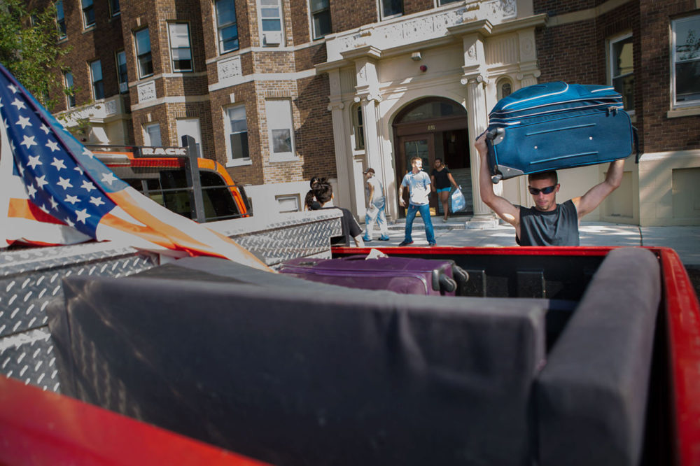 On Monday, Kevin Weldon, a Boston University senior, lifts a suitcase into his pickup truck while helping friends relocate from Comm. Ave. to another apartment in Allston. (Jesse Costa/WBUR)