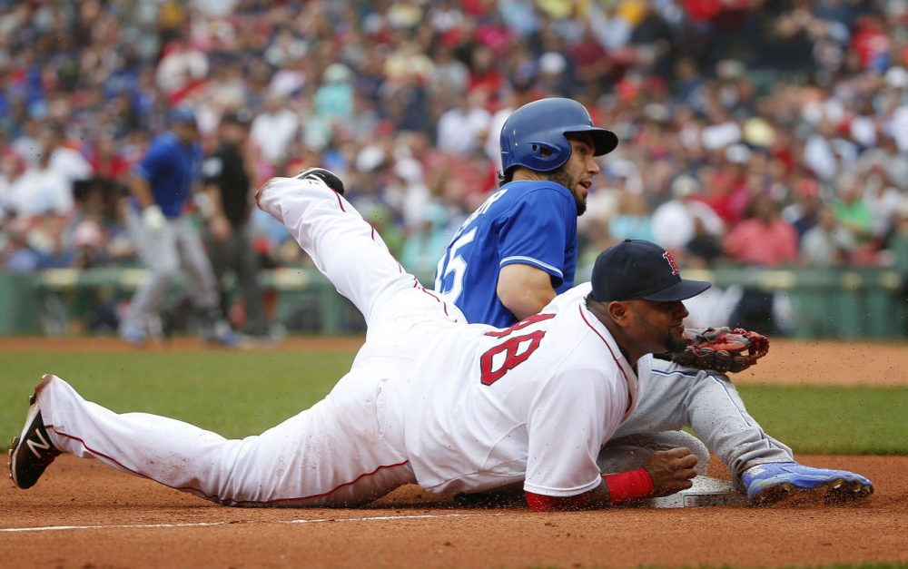 Kansas City Royals' Eric Hosmer and Boston Red Sox third baseman Pablo Sandoval look up after a throw got by Sandoval during the fourth inning of a baseball game at Fenway Park in Boston on Sunday, Aug. 23, 2015. (Winslow Townson/AP Photo)