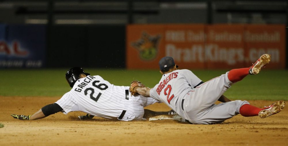 Boston Red Sox shortstop Xander Bogaerts, right, tags out Chicago White Sox's Avisail Garcia,left, at second, as Garcia tries to stretch his single to a double but slid past the base during the sixth inning of a baseball game Monday, Aug. 24, 2015, in Chicago. (Charles Rex Arbogast/AP Photo)