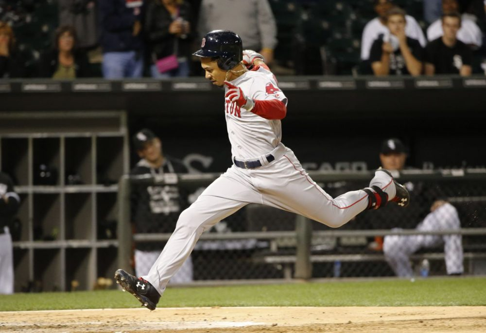 Boston Red Sox's Mookie Betts scores on his double and a throwing error by Chicago White Sox shortstop Alexei Ramirez, during the third inning of a baseball game Tuesday, Aug. 25, 2015, in Chicago. (Charles Rex Arbogast/AP Photo)