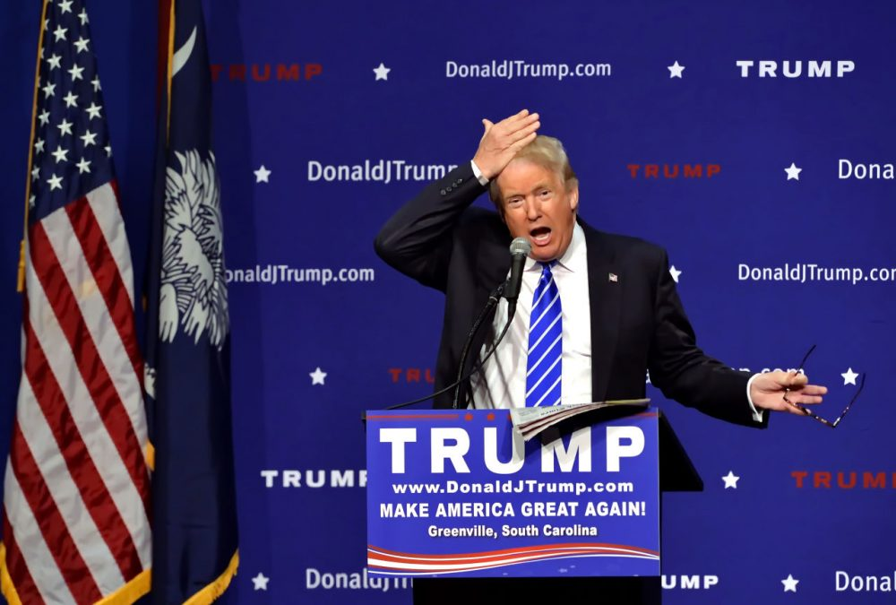 Republican presidential candidate Donald Trump pulls his hair back to show that it is not a toupee while speaking during a rally at the TD Convention Center Thursday in Greenville, S.C. (Richard Shiro/AP)
