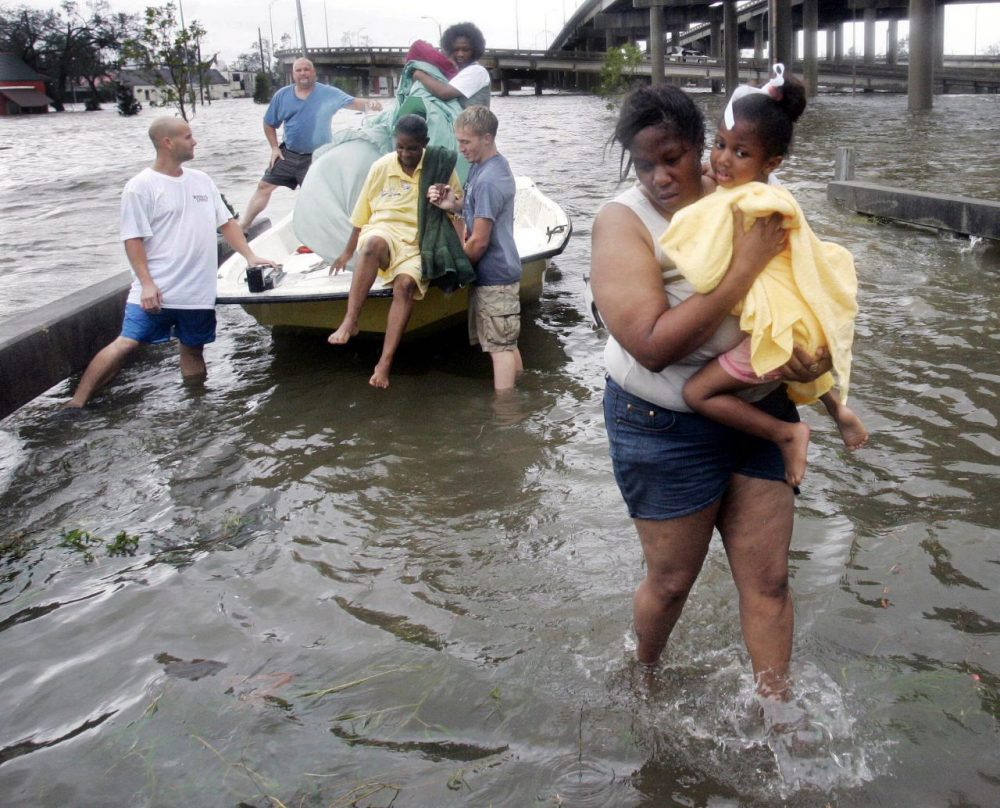 Shante Gruld carries Janeka Garner, 5, to safety after they were rescued from their flooded home by boat in New Orleans, Monday morning, Aug. 29, 2005. (Eric Gay/AP)
