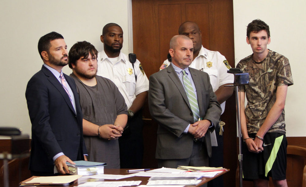 James Stumbo, second from left, and Kevin Norton, right, stand during their arraignment at Boston Municipal Court on Aug. 24 with their lawyers. They were arrested on firearms charges after allegedly threatening the Pokémon World Championships in Boston. (Chitose Suzuki/Boston Herald via AP, Pool)