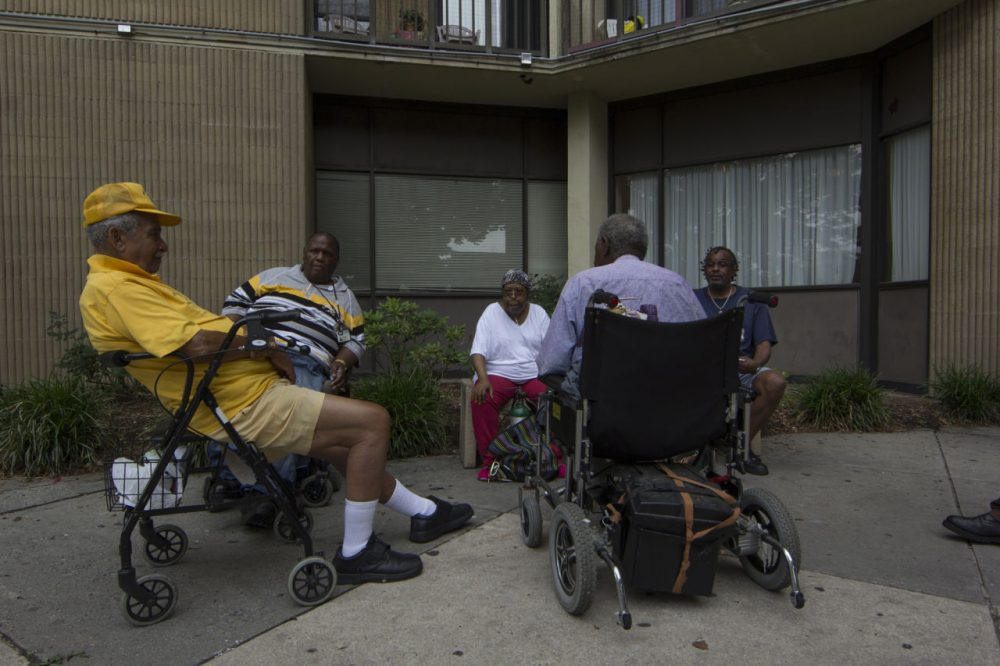 A group of friends sit in front of Bel Park Towers in Park Heights. Many of the folks in this picture spent a lot of time telling me about their concerns and the conditions of their building. (Jonna McKone/ WYPR)