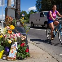 A bicyclist rides past the Boston intersection of Mass. Ave. and Beacon Street, where Anita Kurmann, 38, was hit and killed in a crash on August 7, 2015. Mourners have placed flowers at the scene. (Hadley Green for WBUR)