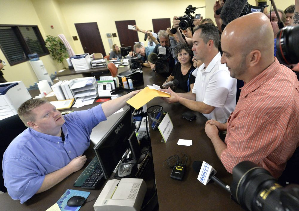Rowan County deputy clerk Brian Mason, left, hands James Yates, and his partner William Smith Jr., their marriage license at the Rowan County Judicial Center in Morehead, Ky., Friday, Sept. 4, 2015. After four attempts, Yates and Smith were finally issued their marriage license. (Timothy D. Easley/AP)