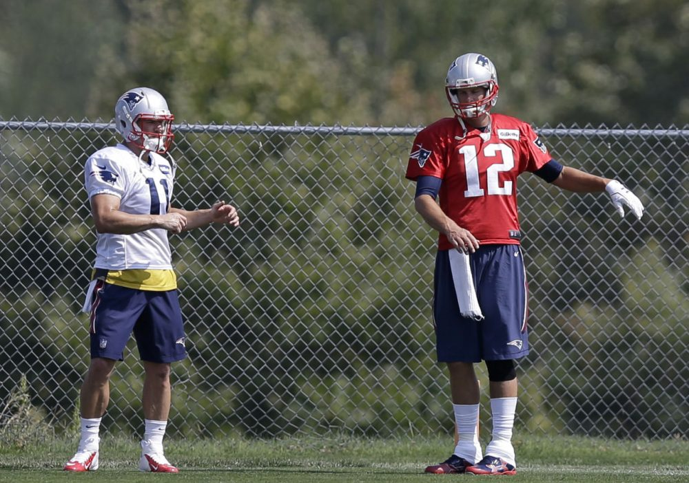 New England Patriots wide receiver Julian Edelman, left, and quarterback Tom Brady, right, stretch as they warm up on the field during an NFL football practice in Foxborough. (Steven Senne/AP)