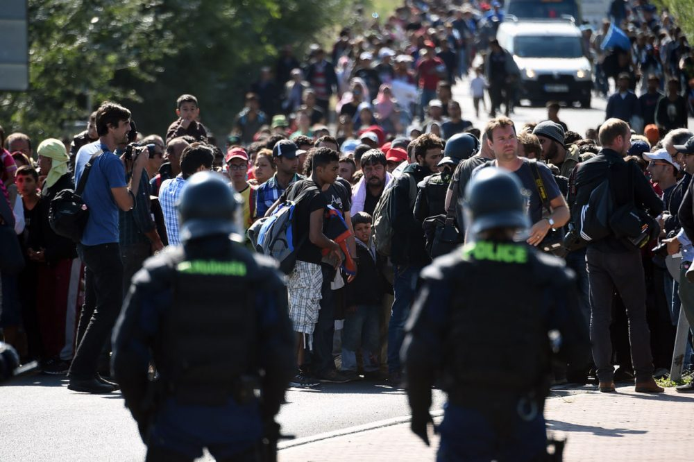 Hungarian riot police officers stand in front of migrants at a collection point at Roszke village at the Hungarian-Serbian border on September 9, 2015. Some 400-500 migrants on Wednesday broke through police lines in Hungary near the main crossing point from Serbia, AFP reporters at the scene said. (Attila Kisbenedek/AFP/Getty Images)