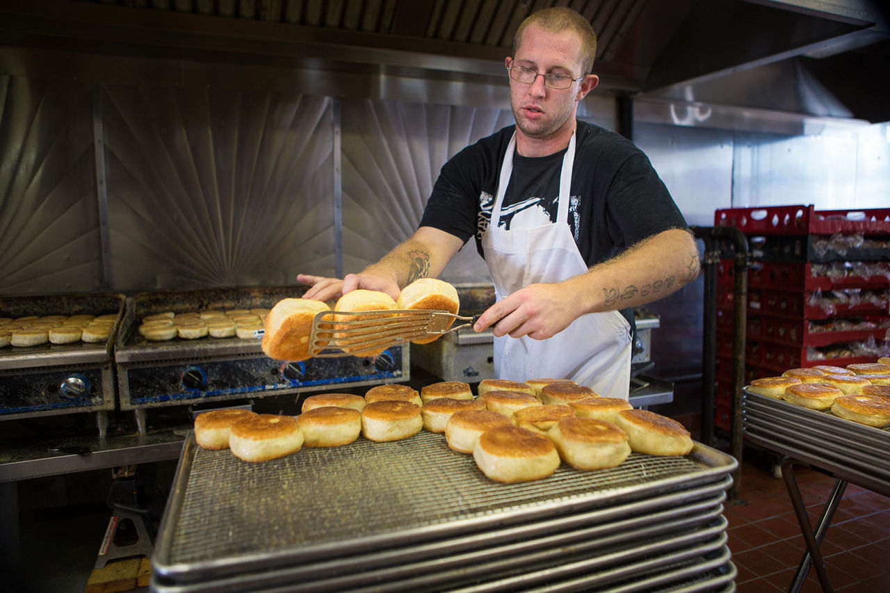 Stone & Skillet's Joe Howland takes hot English muffins off the griddle to cool. (Jesse Costa/WBUR)