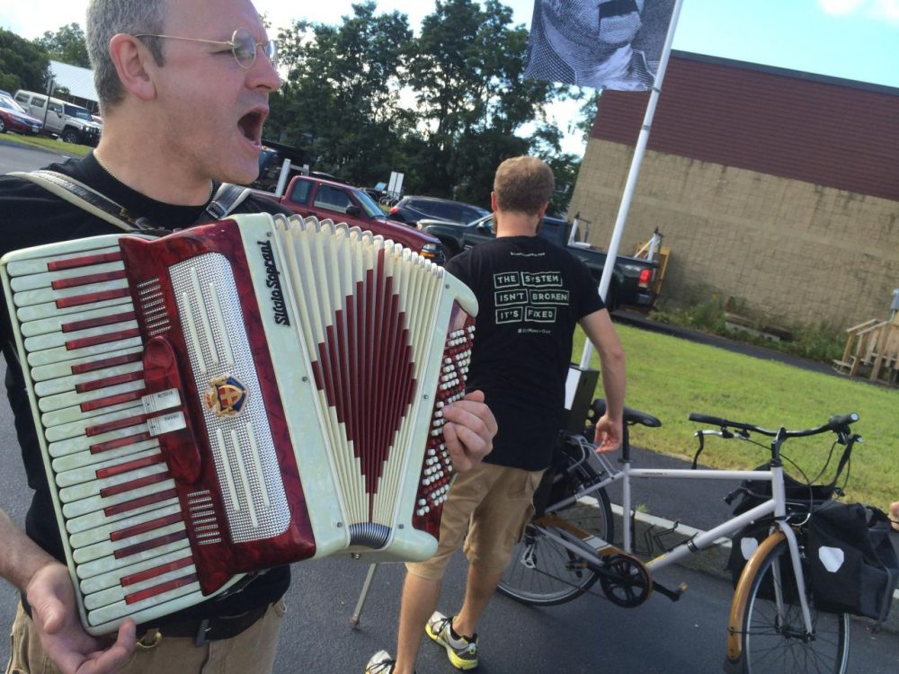 Johnny Clockworks, a member of the Stamp Stampede, performs a song he composed about campaign finance reform at a recent event for Sen. Bernie Sanders. The Stampede is one of many advocacy groups vying for attention in the shadow of the N.H. primary. (Sam Evans-Brown, NHPR)