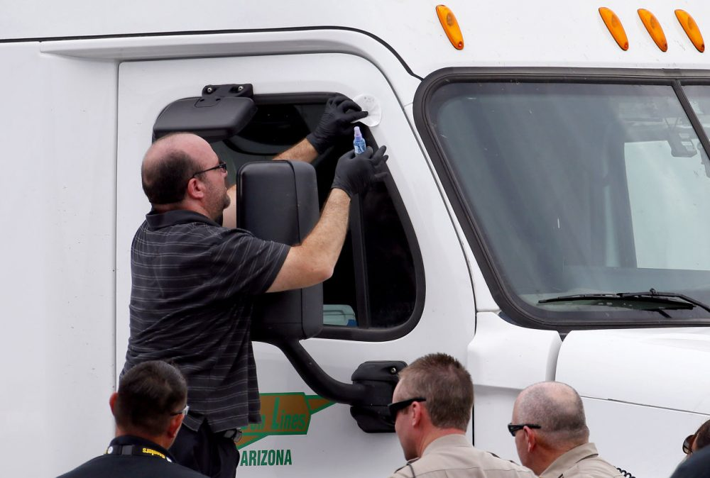 Arizona Department of Public Safety officers inspect a tractor trailer with a bullet hole in the passenger door shortly after it was shot near 67th Ave and I-10, Thursday, Sept. 10, 2015 in Phoenix. Numerous shootings of vehicles along I-10 over the past two weeks have investigators working around the clock to find a suspect in a spate of recent Phoenix freeway shootings that have rattled nerves and heightened fears of a possible serial shooter. (AP Photo/Matt York)