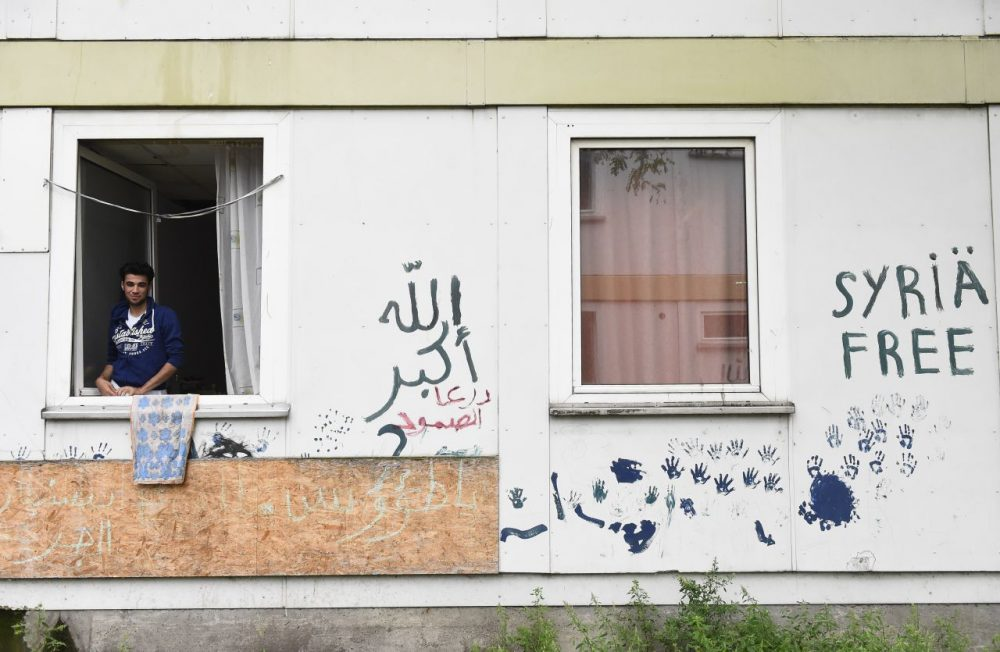 Syrian refugee Abd Alrazak, a 21-year-old from Homs, looks out of the window of his room at a temporary refugee home in Berlin's Spandau district. (Tobias Schwarz/AFP/Getty Images)
