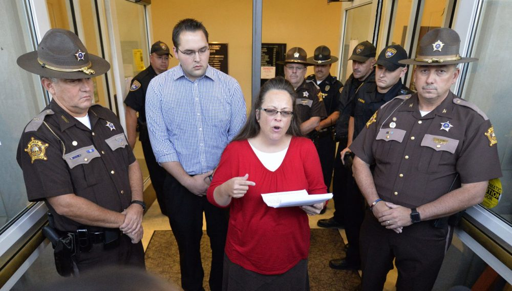 Surrounded by Rowan County Sheriff's deputies, Rowan County Clerk Kim Davis, center, with her son Nathan Davis standing by her side, makes a statement to the media at the front door of the Rowan County Judicial Center in Morehead, Ky., Monday, Sept. 14, 2015. Davis announced that her office will issue marriage licenses under order of a federal judge, but they will not have her name or office listed. (Timothy D. Easley/AP)