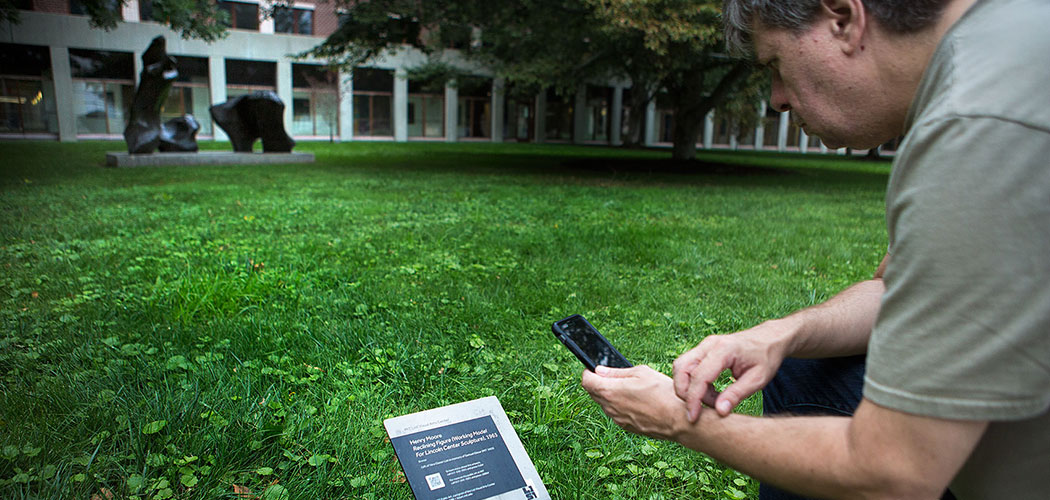 MIT List Visual Arts Center social media coordinator Mark Linga demonstrates how a QR reader plays an audio file on his phone that corresponds to a piece of art. (Jesse Costa/WBUR)