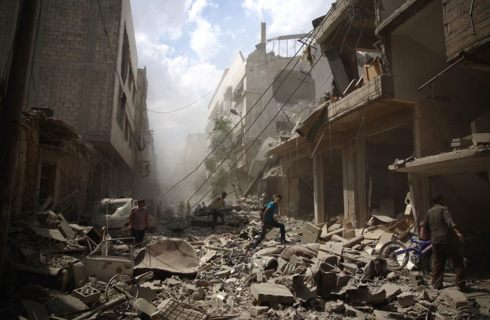 Syrians walk amid the rubble of destroyed buildings following reported air strikes by regime forces in the rebel-held area of Douma, east of the capital Damascus, on August 30, 2015. More than 240,000 people have been killed since Syria's conflict began in March 2011, and half of the country's population has been displaced by the war.  (ABD Doumany/Getty Images)