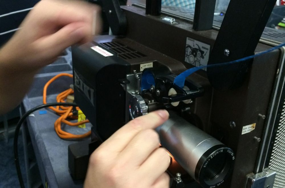 Barron Sherer feeds 16mm film into a projector at Miami International Airport. (Wilson Sayre/WLRN)