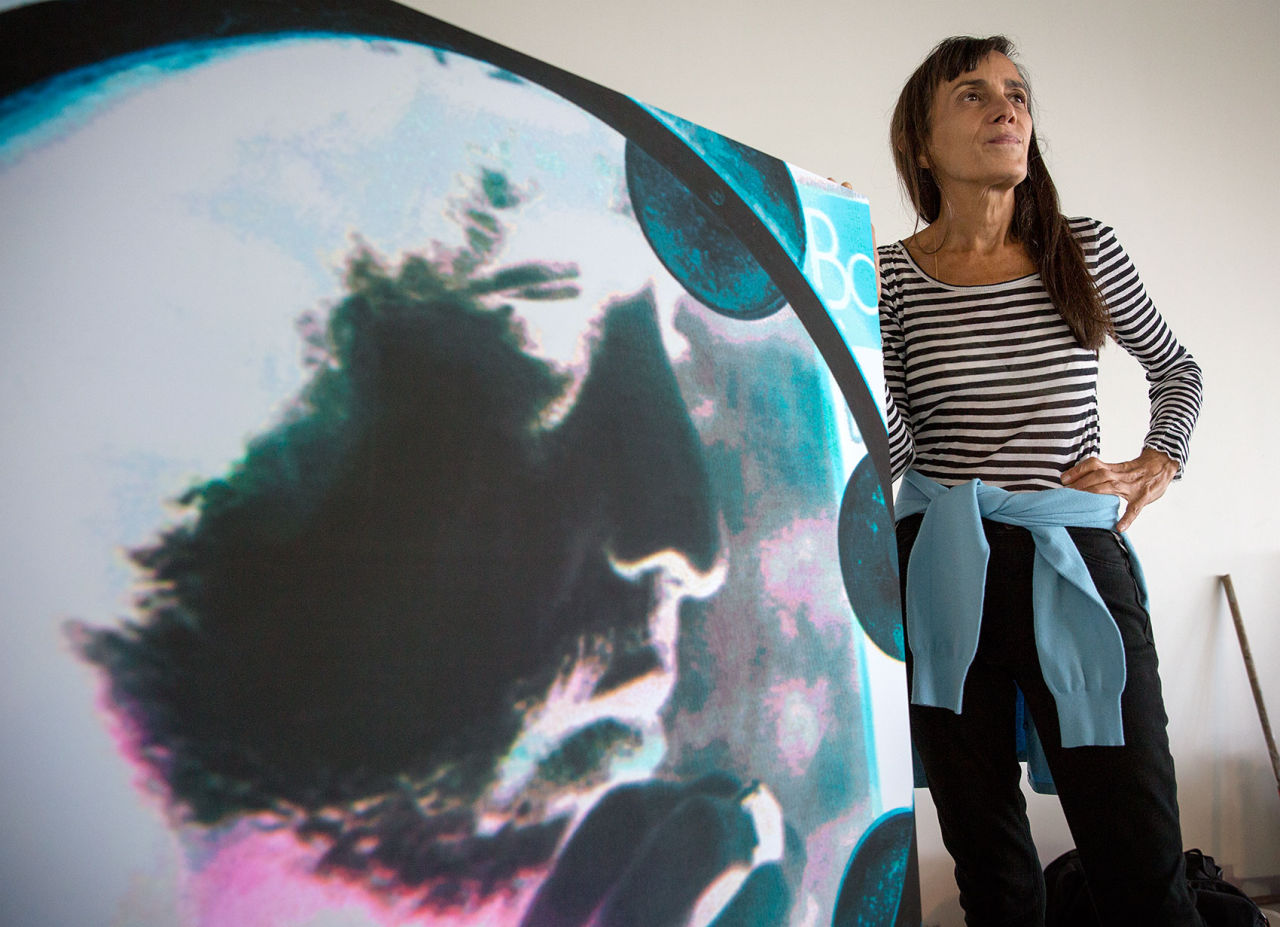 """Artist Lesley Schiff stands beside one of her images from the exhibit """"LIT: A Portrait of Bob Dylan."""" (Robin Lubbock/WBUR)"""