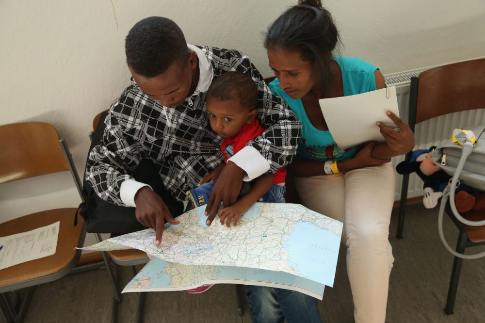 A young migrant couple from Eritrea look on a map of Europe as they prepare to depart with their son after they completed the registration process at a center for migrants at a facility of the German Federal Police (Bundespolizei) on August 31, 2015 in Rosenheim, Germany. (Sean Gallup/Getty Images)