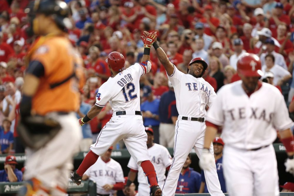 Rougned Odor #12 of the Texas Rangers is congratulated by Elvis Andrus after hitting a two run home run during the first inning of a baseball game against the Houston Astros at Globe Life Park on September 16, 2015 in Arlington, Texas. (Brandon Wade/Getty Images)