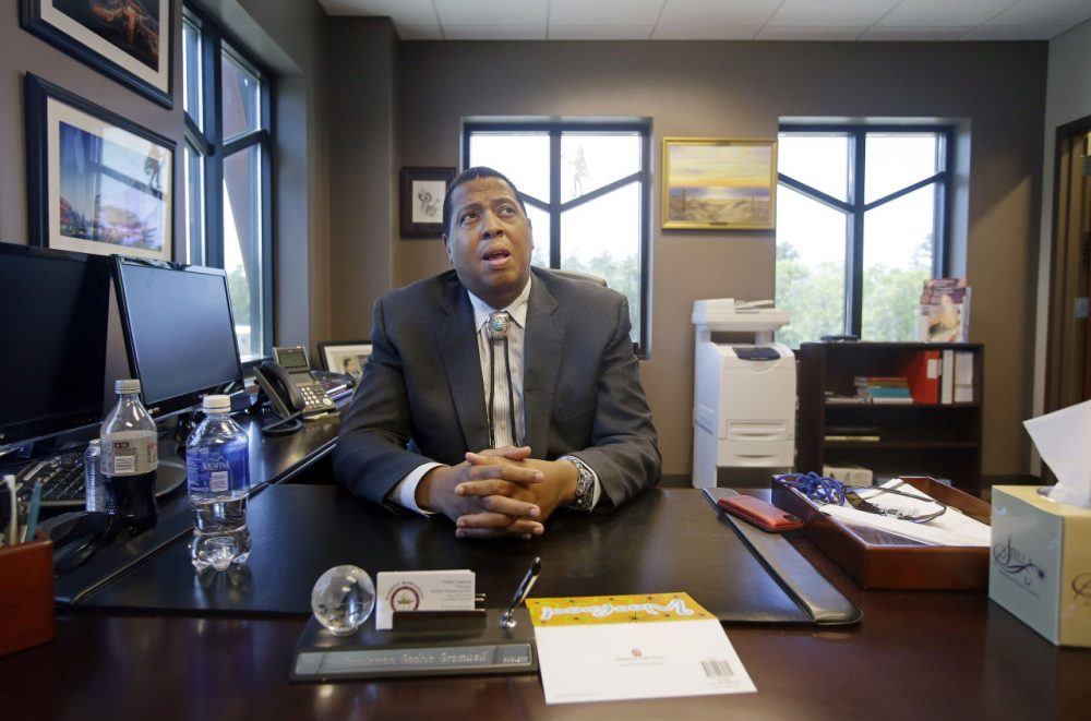 In this May 29, 2014 photo, Mashpee Wampanoag Tribe Chairman Cedric Cromwell sits behind his desk at the community/government Center in Mashpee.(Stephan Savoia/AP)