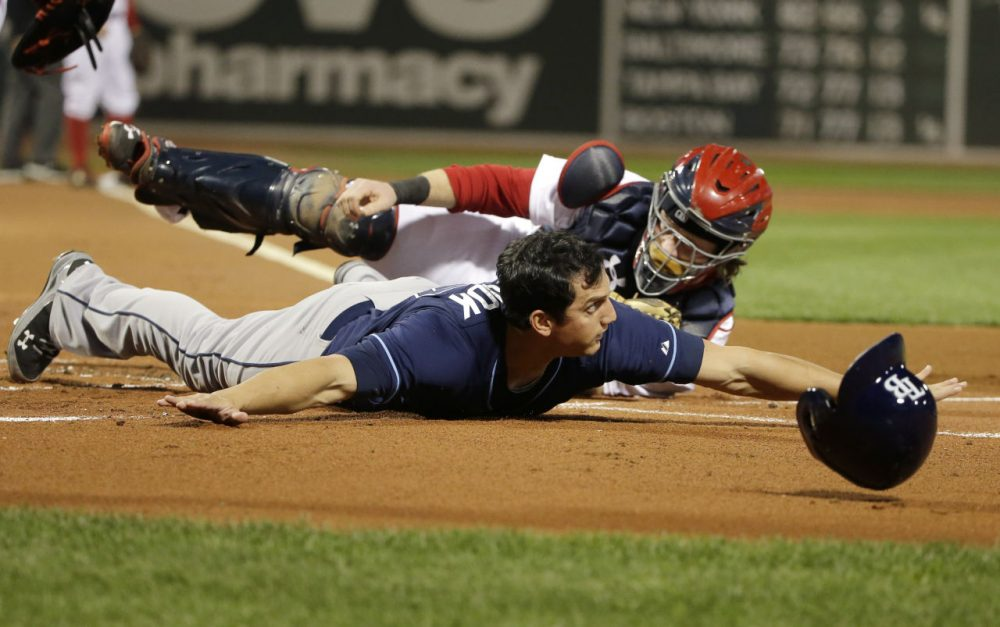 Tampa Bay Rays' Mikie Mahtook, left, slides safe at home plate as Boston Red Sox catcher Ryan Hanigan, right, tries to tag him in the first inning of a baseball game, Monday, Sept. 21, 2015, at Fenway Park, in Boston. (Steven Senne/AP)