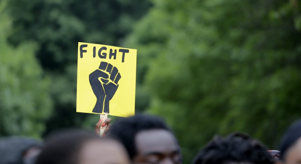 A woman holds up a sign as hundreds take part in a march in memory of VonDerrit Myers Jr., on Saturday, Aug. 8, 2015, in St. Louis. Myers, a black 18-year-old shot and killed last October by an off-duty St. Louis police officer. The city prosecutor in May announced the officer acted in self-defense after being fired upon by Myers while an attorney for Myers' family says Myers was not armed. (Jeff Roberson/AP)