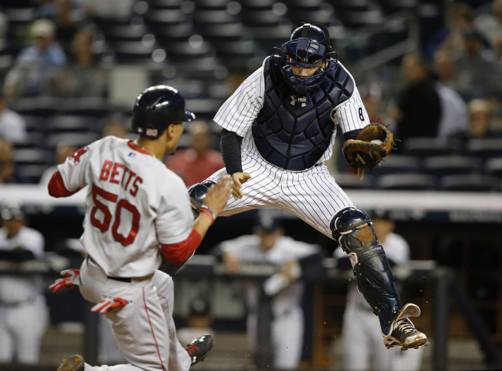 Boston Red Sox's Mookie Betts (50) tries to score as New York Yankees catcher John Ryan Murphy drops to the plate after catching a high throw on a first-inning fielder's choice in New York Monday. (Kathy Willens/AP)