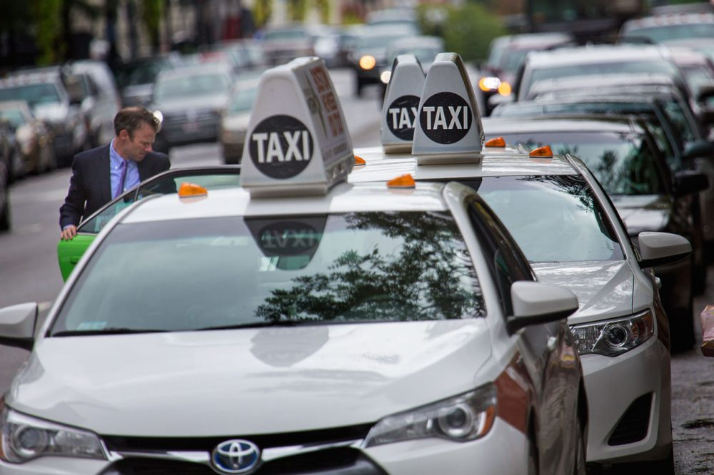 A man jumps into one of a line of taxis at a taxi stand on Boylston Street. (Jesse Costa/WBUR)